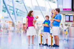 Big family at the airport. Big happy family with three kids traveling by airplane at Dusseldorf International airport, parents with teenager boy, toddler girl Royalty Free Stock Photos