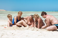 Big Family on the Beach. Members of a big family are sitting by the sea and building sand castle Stock Photography