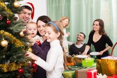 Big family celebrating Xmas. Big multigenerational family decorating Xmas tree and set table royalty free stock image