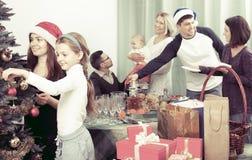 Big family celebrating Xmas. Portrait of big multigenerational family decorating Xmas tree and set festive table royalty free stock photo