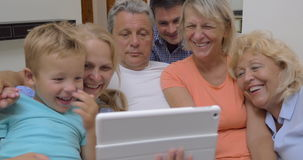 Big family with child watching tablet computer. Family with parents, son and grandparents watching something on touch pad ad smiling stock footage