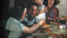 1951: Big family at crowded dinner table eat Italian food. NEWARK, NEW JERSEY. Vintage 8mm film home movie professionally cleaned and captured in 4k (3840x2160 stock video
