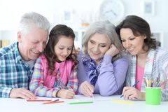 Big family with cute little girl doing homework. Together Stock Images