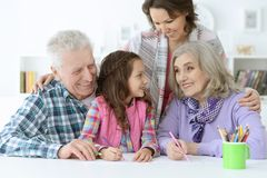 Big family with cute little girl doing homework. Together Stock Photos