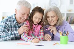 Big family with cute little girl doing homework. Together Royalty Free Stock Photo