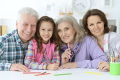 Big family with cute little girl doing homework. Together Stock Photo