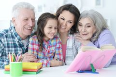 Big family with cute little girl doing homework. Together Royalty Free Stock Images
