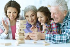 Big family with cute little girl playing with wooden blocks. Together Stock Photography