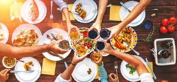 Big family dinner. Vertical top view on served table and hands w