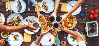 Big family dinner. Vertical top view on served table and hands w. Ith clinking goblets stock image