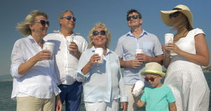 Big family drinking sea from paper cups by the sea. Young parents, little son and grandparents in sunglasses drinking tea or coffee from plastic cups. Sea and stock footage