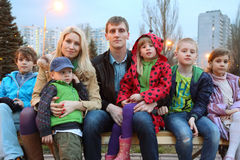 Big family in evening sitting on the bench. Big happy family of seven in the evening sitting on the bench stock image
