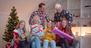 Big family give each other Christmas presents sitting on the couch, Christmas tree family idyll