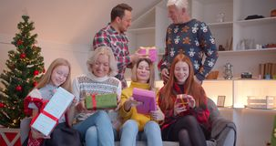 Big family give each other Christmas presents sitting on the couch, Christmas tree family idyll gift