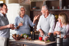 Big family having a conversation in the kitchen. Happy days. Delighted big friendly family having a meal while talking in the kitchen and drinking Stock Image
