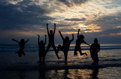 Big family jumping on the beach at dusk Royalty Free Stock Images
