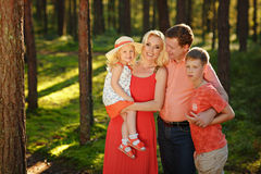 A big family: mom, dad and their babies smile in the forest in t. He sunny summer Stock Photo