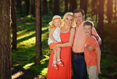 A big family: mom, dad and their babies smile in the forest in t. He sunny summer Stock Images
