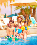 Big family near poolside. Big family relaxed near poolside, happy young mother with three sweet child have fun outdoors on tropical resort, summer vacation Royalty Free Stock Photos