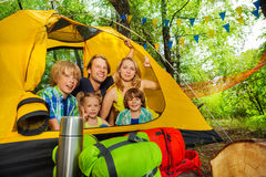 Big family portrait looking happy outside of tent stock photography