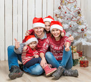 Big family in red santa hats near the christmas tree Stock Photos