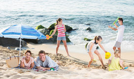 Big family resting on beach. Portrait of happy men and women resting on beach with four kids playing with sand toys and badminton Stock Photo