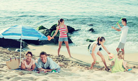 Big family resting on beach. Portrait of happy men and women resting on beach with four kids playing with sand toys and badminton Stock Photos