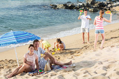 Big family resting on beach stock images