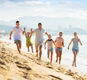 Big family running on beach. Portrait of cheerful men and women with four kids having fun and running on sandy beach Stock Photos