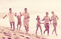 Big family running on beach. Portrait of cheerful men and women with four kids having fun and running on sandy beach together Royalty Free Stock Photos