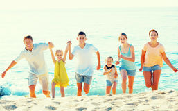 Big family running on beach. Portrait of happy big family, men and women with four kids, having fun and running on sandy beach Stock Images