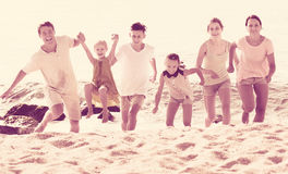 Big family running on beach. Portrait of positive big family, men and women with four kids, having fun and running on sandy beach Stock Photos