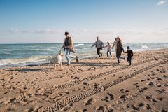 big multigenerational family running with labrador dog on beach stock photo