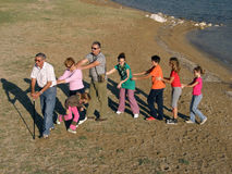Big family on sandy beach. Portrait of  group of people of different generations - grandparents, grandchildren, daughter, son walk, dancing  together on sand Stock Images