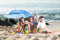 Big family on sandy coast. Portrait of cheerful men and women with four kids having beach umbrella and toys on sandy coast Royalty Free Stock Photos