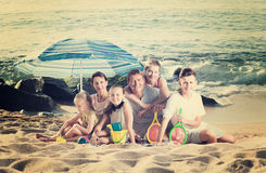 Big family on sandy coast. Portrait of cheerful men and women with four kids having beach umbrella and toys on sandy coast Stock Image