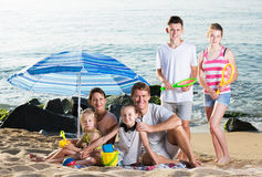 Big family on sandy coast. Portrait of positive big family - men and women with four kids having beach umbrella and toys on sandy coast. Focus on man Stock Photography