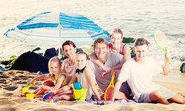 Big family on sandy coast. Portrait of smiling men and women with four kids having beach umbrella and toys on sandy coast. Focus on man Stock Photography
