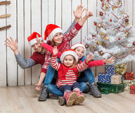 Big family in santa hats near the christmas tree Stock Images