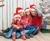 Big family in santa hats near the christmas tree Royalty Free Stock Image