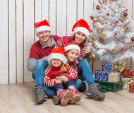 Big family in santa hats near the christmas tree Royalty Free Stock Photos