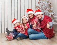 Big family in santa hats near the christmas tree Royalty Free Stock Image