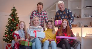 Big family sitting on the couch with Christmas gifts portrait happiness idyll