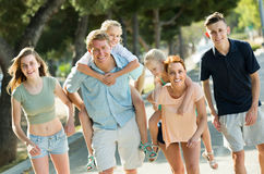 Big family of six people walking with kids on parents back in su Stock Images