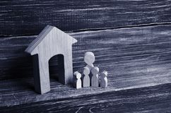 Big family is standing near the house. Wooden figures of persons. Stand near a wooden house. The concept of a couple in love, cohabitants, parents, buyers and stock images