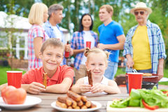 Big family on vacations. Children eating sausages during their family gathering Royalty Free Stock Photos