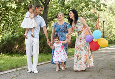 Big family walk in summer city park, parents with child and grandmother, summer season, green grass and trees Royalty Free Stock Photography