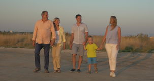 Big family walking in the countryside at sunset. Steadicam shot of grandparents and parents with little son walking on rural road at sunset. Family outing in the stock footage