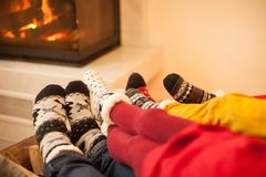 Big family is warming near the fireplace stock images