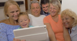 Big family watching something on touch pad. Child, parents and grandparents looking at tablet computer. They watching something interesting on the screen stock video